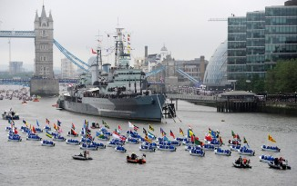 A flotilla of wooden rowing boats led the procession to Tower Bridge from Putney.